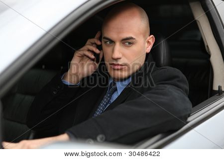 Businessman using a phone in his car
