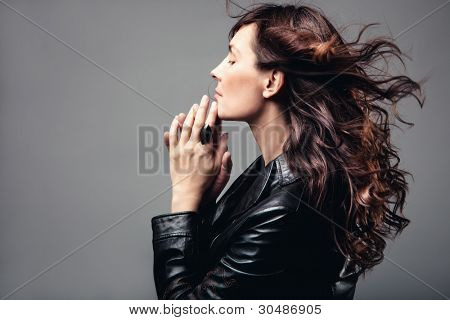 adult woman profile long wavy hair in motion, hands touching chin, studio shot