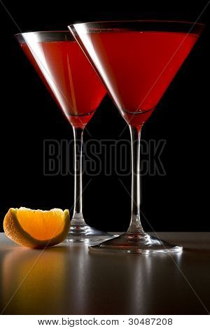 Red Cocktails in Martini Glasses with Orange Wedge
