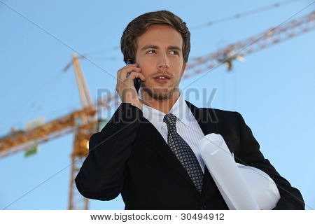 Architect on site with plans and cellphone