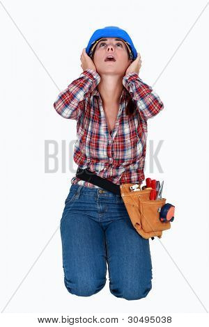 A female construction worker covering her ears.