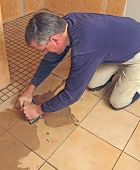 stock photo of grout  - Man grouting ceramic tile - JPG