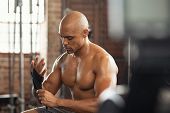 Black bodybuilder wearing strap on wrist preparing for intensive workout session at crossfit club. A poster