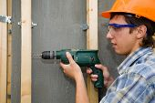 stock photo of hand tools  - The building worker holds a manual drill in hands - JPG