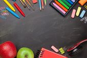 School education supplies on chalkboard backdrop. Back to school template concept. Top view flat lay poster