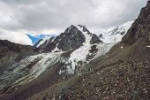 Snowy Giant Mountain Range Under Cloudy Sky. Rocky Ridge With Snow. Huge Glacier. Icy Mountainside W poster