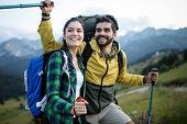 Couple - Active Hikers Hiking Enjoying View Looking At Mountain Forest Landscape poster
