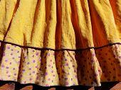 Hem Of Baby Girl Yellow Skirt With Folds & Floral Pattern. Cozy Lovely Little Girl Skirt Hem Decorat poster