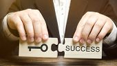 Businessman Collects Wooden Puzzles Key To Success. Concept Of Achieving The Goal, Overcoming Diffic poster