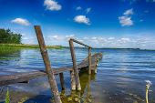 Old Rickety Wooden Jetty Leading Into A Lake poster