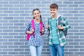 Two Happy Schoolchildren With Backpacks Against A Brick Wall Outdoors. Cute Children - Pupils Teen G poster