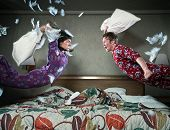 picture of pajamas  - Feathers fly as a young couple dressed in generic pattern one-piece pajamas, engage in a pillow fight.