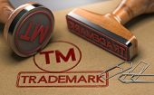 3d Illustration Of Two Rubber Stamps With The Word Trademark And The Symbol Tm Over Brown Paper Back poster