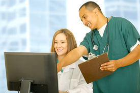 stock photo of medical assistant  - nurse in medical uniform pointing at computer screen with his assistant sitting down - JPG