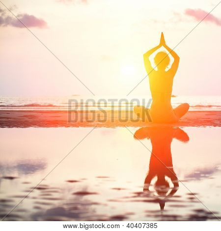 Yoga woman sitting in lotus pose on the beach during sunset, with reflection in water (bright colors)