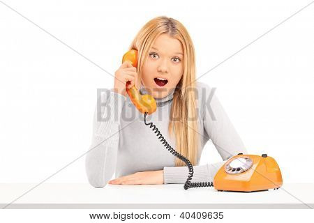 Young excited woman talking on a telephone isolated on white background