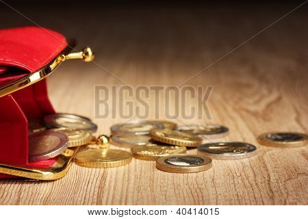 female red wallet with coins on wooden background