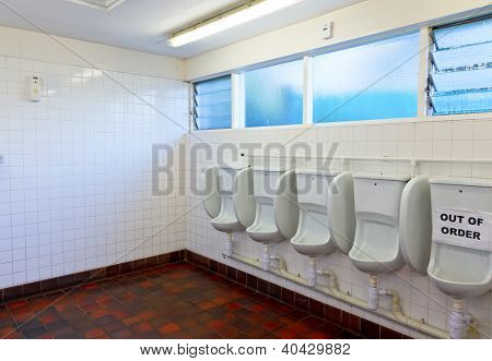Empty public lavatory with urinal out of order