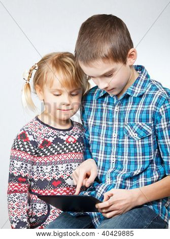 Boy shows little sister how to use a touch pad