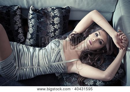 stylish young woman lie on pillows in living room