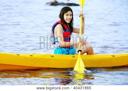 Biracial Teen girl in yellow kayak on lake