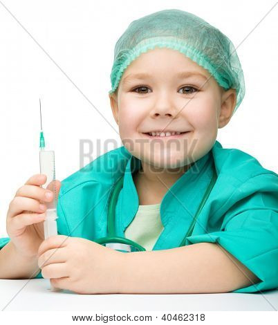 Cute little girl is playing doctor with syringe, isolated over white
