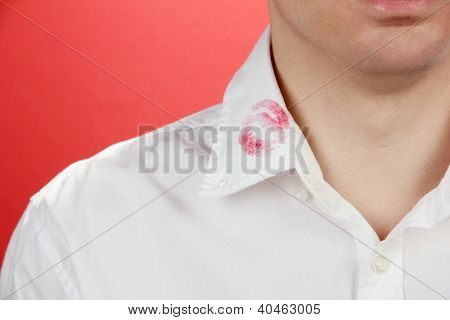 Lipstick kiss on shirt collar of man, on red background