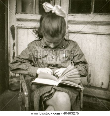 Vintage photo of young girl in scout uniform reading a book, early sixties