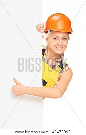 Female manual worker giving a thumb up and standing behind blank panel, isolated on white background