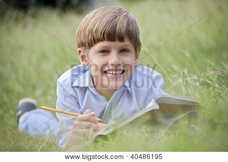 Happy School Boy Doing Homework And Smiling, Lying On Grass