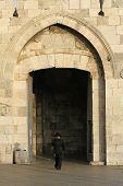 stock photo of tora  - orthodox Jew entering Jerusalem old city through the Jaffa gate - JPG