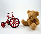 foto of teddy-bear  - a teddy bear and a red cast iron tricycle - JPG