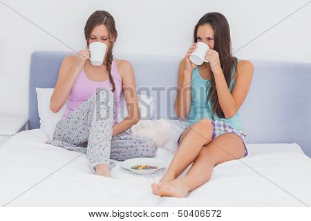 Friends chatting and drinking coffee sitting up in bed wearing pajamas