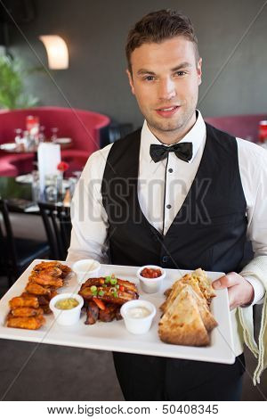 Handsome waiter serving appetizing finger food platter in classy restaurant