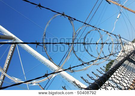 Barbwire and razor wire against blue sky