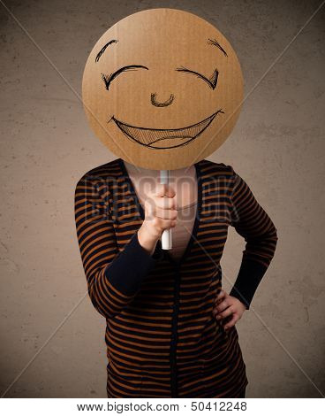 Young lady holding a cardboard smiley face emoticon in front of her head