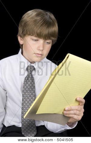 Boy In Business Dress Reading Notepad