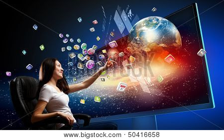 Young woman in armchair pushing icon on media screen. Elements of this image are furnished by NASA