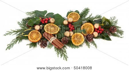 Christmas floral arrangement with gold bauble decorations, dried orange fruit, spice with holly and winter greenery over white background.
