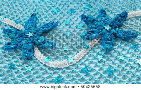 Two Blue Crocheted Flower On A Blue Background