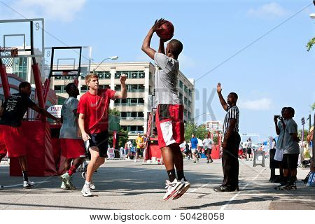 Young Man Shoots Jump Shot In Street Basketball Tournament