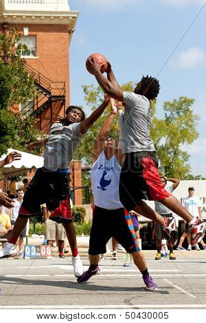 Three Men Fight For Rebound In Outdoor Street Basketball Tournament