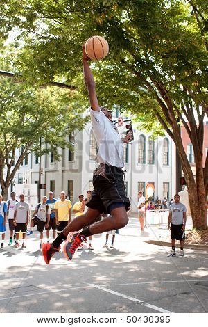 Young Man Leaps To Dunk Basketball During Outdoor Street Tournament