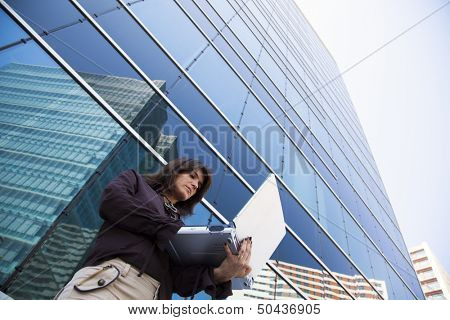 businesswoman working with her laptop next to the office