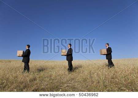 three businessman lineup holding a cardboard box over his head