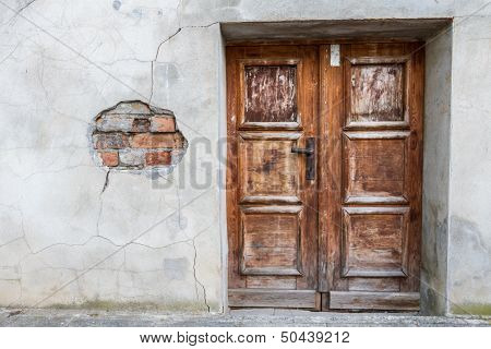 Run-down Wooden Entrance Door With Cracked Brick Wall
