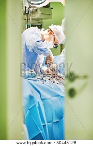 surgeon in uniform perform operation on a patient at cardiac surgery clinic