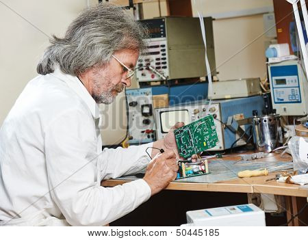 male technicial engineer with microchip plate at test laboratory factory