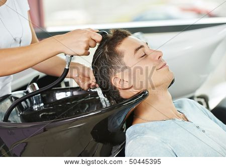 Washing man client hair in beauty parlour hairdressing salon