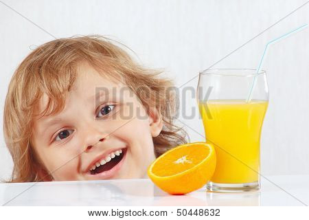 Beautiful smiling child with a glass of fresh juice and orange